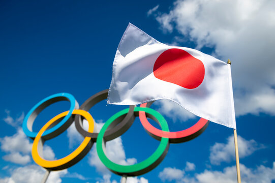 RIO DE JANEIRO - MARCH, 2016: A Japanese flag flutters in the wind in front of Olympic Rings standing under bright blue sky with puffy white clouds