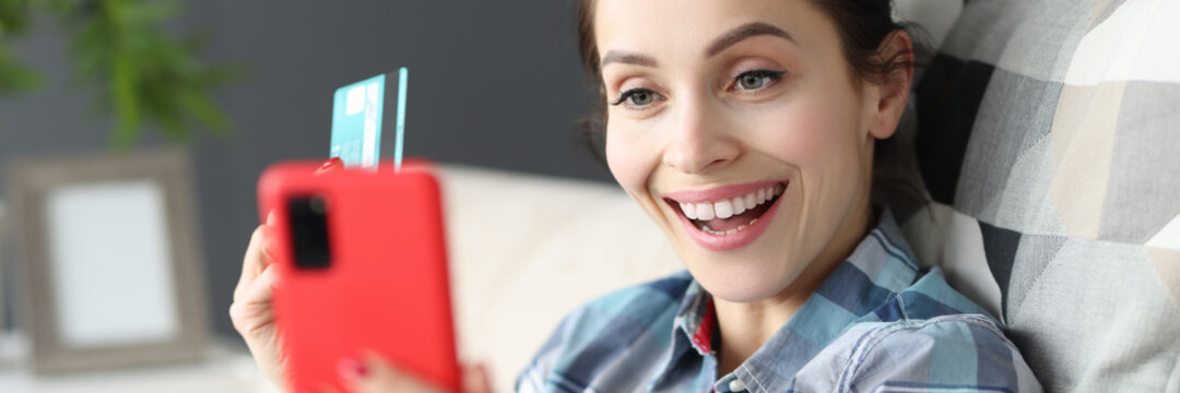 Happy woman holding mobile phone and credit bank card