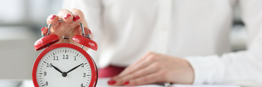 Woman sitting at table with book and clicking on alarm clock closeup