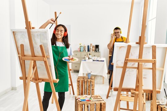 Young hispanic couple smiling happy listening to music and drawing at art studio.