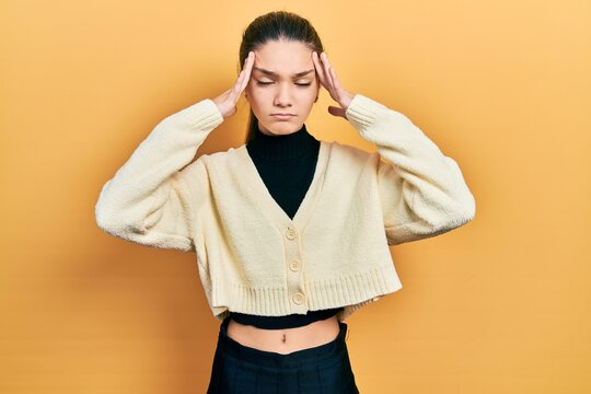 Young brunette girl wearing casual yellow jacket with hand on head, headache because stress. suffering migraine.