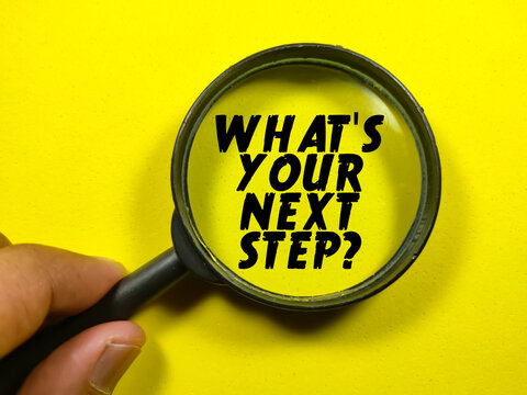 Business concept.Text WHAT'S YOUR NEXT STEP? on magnifying glass on a yellow background.