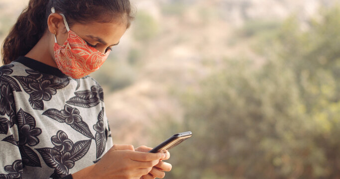 Closeup of a young female South Asian child texting on her phone while wearing an orange Covid mask