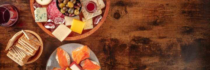 Fototapeta Gourmet wine snacks panorama. A glass of red wine and a platter with olives, blue cheese and other cheeses and hams. Salmon sandwiches and crackers. Antipasti or tapas on a rustic wooden background obraz