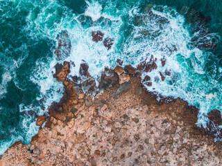 Fototapeta Aerial view of rocky coastline and crashing waves obraz