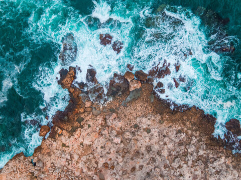 Aerial view of rocky coastline and crashing waves