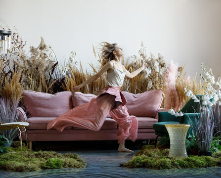 Beauty young woman in a room with sofa in the middle of tall grass