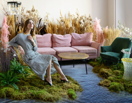 Young woman posing in a living room in the middle of tall grass
