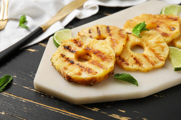 Board with grilled pineapple slices and lime on dark wooden background, closeup
