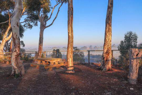 picnic benches in misty morning landscape with view