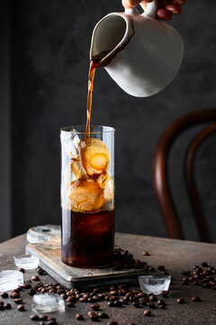 Black coffee into the glass  with ice cubes. Cold caffeine drink for summer day.