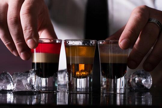 Barman preparing cocktail shots at the bar counter. Barman mixing drinks at the night club...