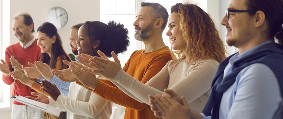 Happy diverse audience clapping hands. Group of excited smiling young and mature people applauding coach, teacher or instructor thanking speaker for interesting, engaging and fun casual presentation