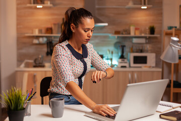 Businesswoman checking time on watch while working from home. Employee using modern technology at...