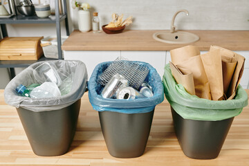 Row of three trash bins with sorted garbage on kitchen table
