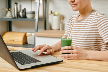 Obraz Contemporary female with drink sitting in front of laptop in the kitchen - fototapety do salonu