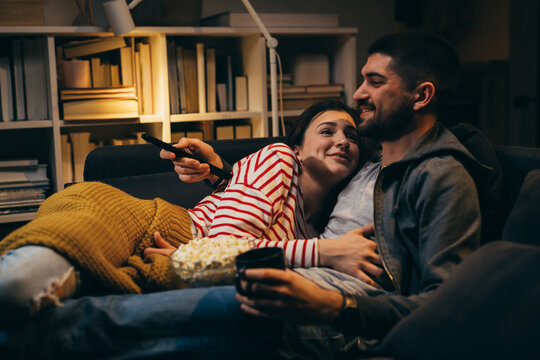 couple enjoying evening at home, watching television