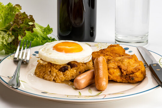 Side view of thai style american fried rice with fried egg, sausages, fried chicken raisin and green vegetables in white ceramic plate.