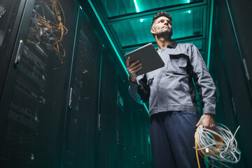 Fototapeta Low angle portrait of mature network engineer using digital tablet in server room during maintenance work in data center, copy space obraz