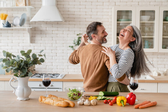 Happy cheerful middle-aged mature couple family parents dancing together in the kitchen, preparing cooking food meal for romantic dinner, spending time together. Active seniors
