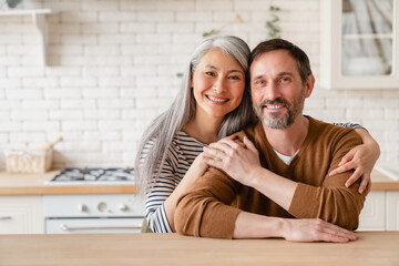 Fototapeta Cheerful happy mature middle-aged caucasian couple family parents husband and wife emracing hugging, spending time together in the kitchen at home, sharing love and care. Social distance concept obraz