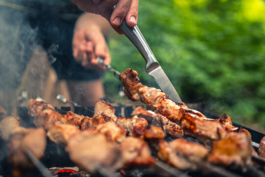 Man hands trying barbecue delicious grilled meat with knife on brazier outdoors. Person preparing pork steaks with smoke on fired charcoals. Hot BBQ closeup with nature on background