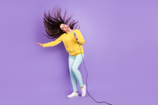 Full length body size view of attractive dreamy cheerful girl throwing hair singing hit isolated over violet purple color background