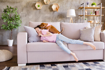 Photo of sweet pretty school girl wear pink t-shirt lying sofa playing dachshund dog indoors house home room Wall mural