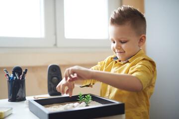 Obraz Boy playing wit his zen garden - fototapety do salonu