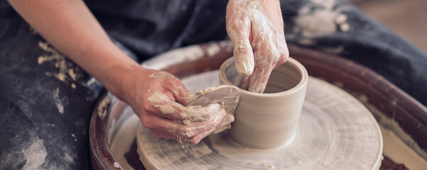 Obraz Close up female hands make dishes from clay. woman hands working on potters wheel. The master potter works in a workshop. banner - fototapety do salonu