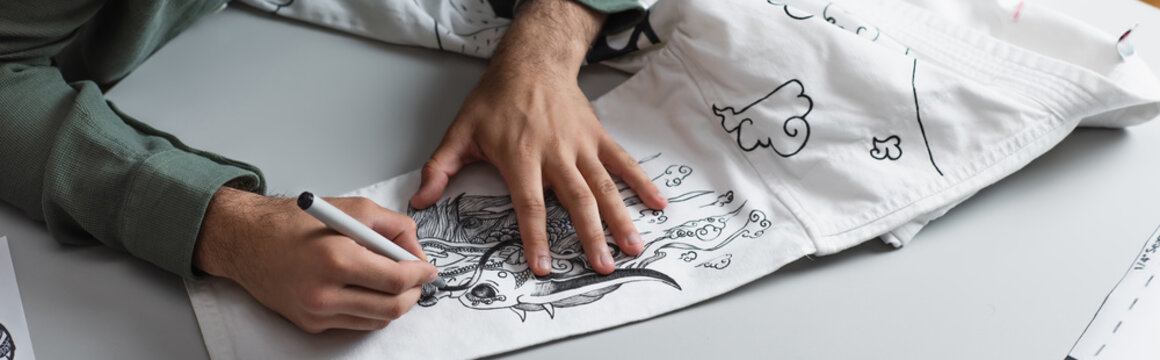 partial view of artist creating traditional drawing on kimono, banner