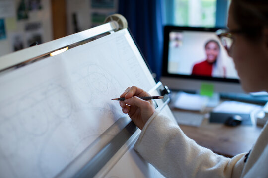 Female architect video conferencing and working at drafting table