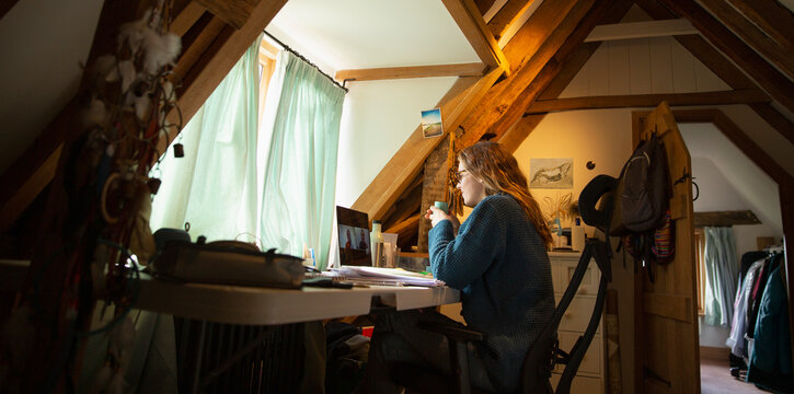 Woman video conferencing at laptop in home office