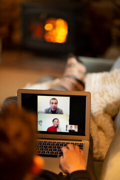 Man video conferencing with colleagues on laptop in living room