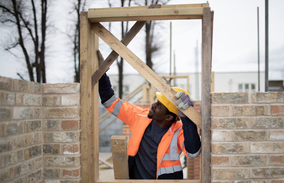 Male construction worker installing door frame at construction site