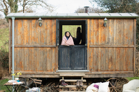 Carefree young woman in tiny cabin rental window