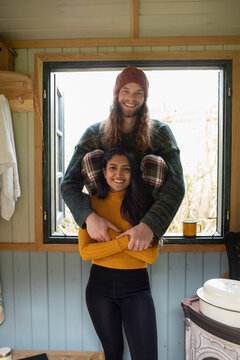 Portrait happy young couple in cabin window