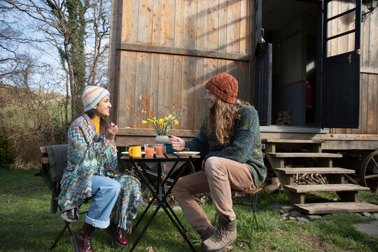 Happy young couple eating outside tiny cabin rental