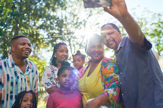 Happy multigenerational family taking selfie in sunny park