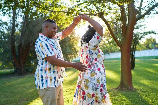 Happy couple dancing in summer backyard