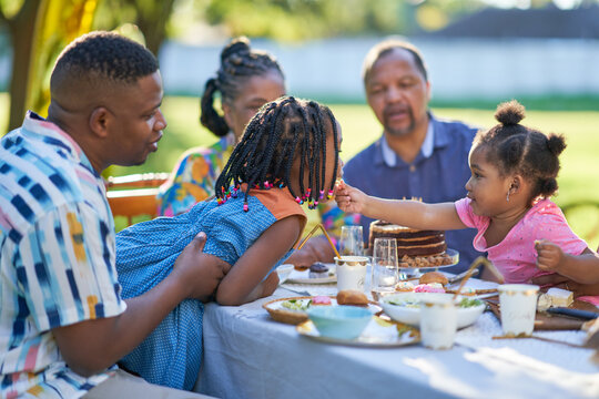 Multigenerational family celebrating birthday at patio table