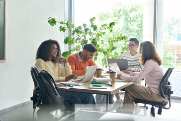 Young happy creative team group four multicultural coworkers students brainstorming working on...