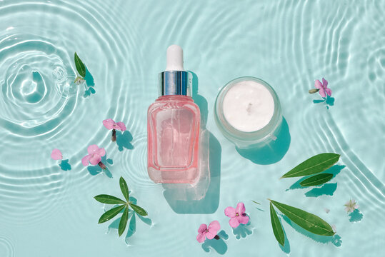 Set moisturizing cosmetic products on water with drops. Serum glass bottle and cream on aqua surface