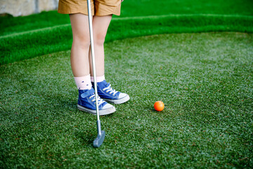 Cute preschool girl playing mini golf with family. Happy toddler child having fun with outdoor activity. Summer sport for children and adults, outdoors. Family vacations or resort.