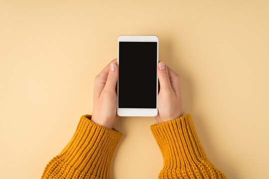First person top view photo of female hands in yellow sweater holding white smartphone on isolated pastel orange background with copyspace