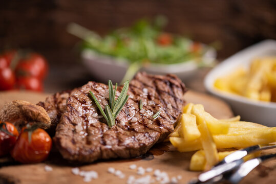 Sliced grilled medium rare beef steak served with fries