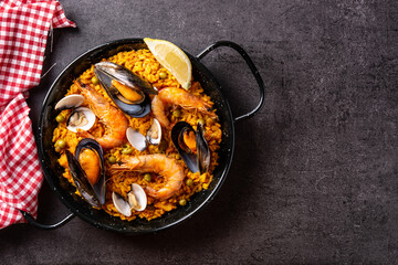 Fototapeta Traditional spanish seafood paella on black background. Top view. Copy space obraz