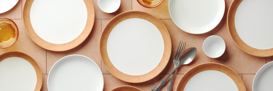 Mockup background for food stylist presentation. Top view of empty plates with tableware setting on beige terracotta background. 3d render illustration. Clipping path of each element included.