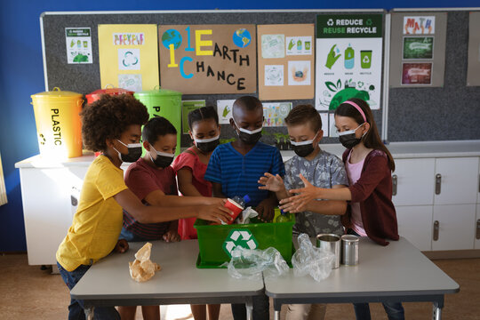 Group of diverse students wearing face masks putting recyclable plastic items in tray at school