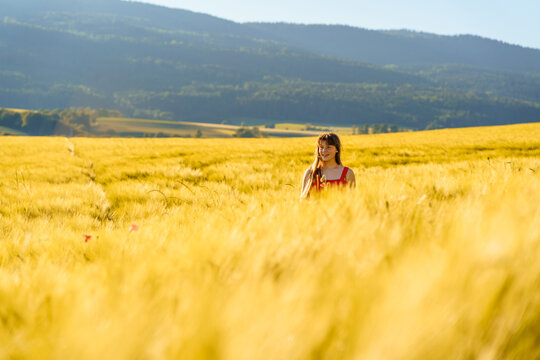 Pretty teenager girl with long hair enjoying nature at sunny summer day in yellow barley field in countryside. Healthy holidays lifestyle.